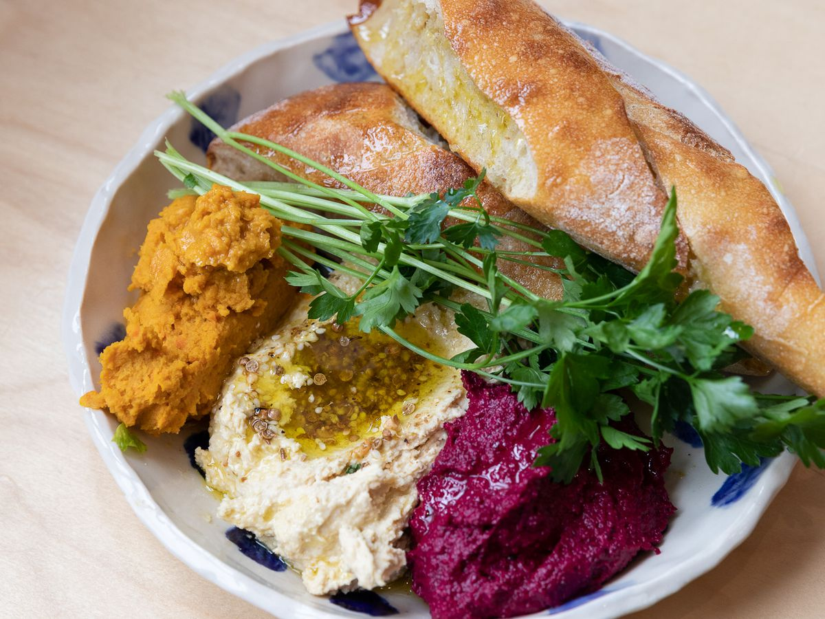 A dish filled with beet hummus, regular hummus, and orange lentil dip with parsley springs and three slices of crusty bread.