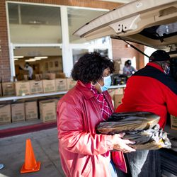 Mary Ann Sampson carries packages of chicken to a waiting car while she helps distribute foodat Calvary Baptist Church in Salt Lake City on Saturday, Dec. 19, 2020.