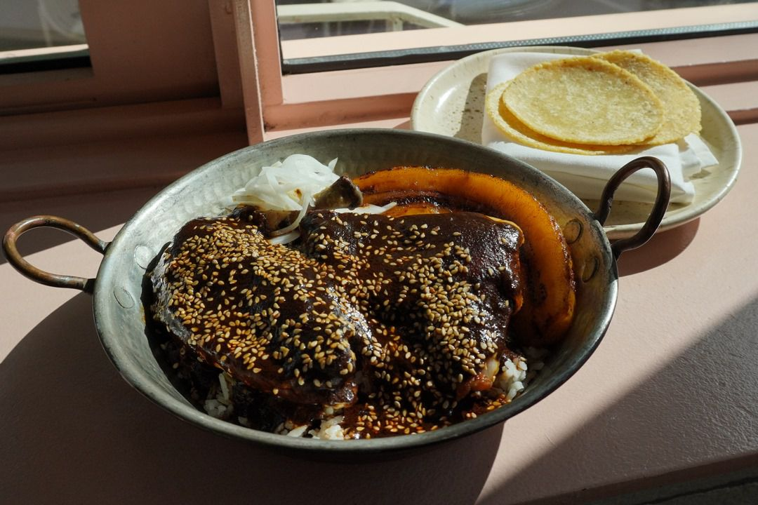 Chicken covered in dark brown mole and lighter brown seeds, placed in a shallow metal serving vessel with round handles, next to a plate with tortillas, on top of a pink surface