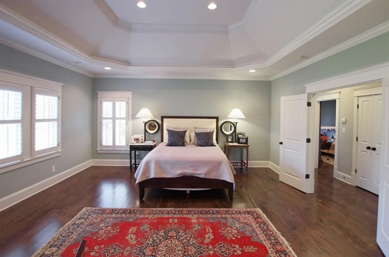 A large bedroom space with white and green walls.