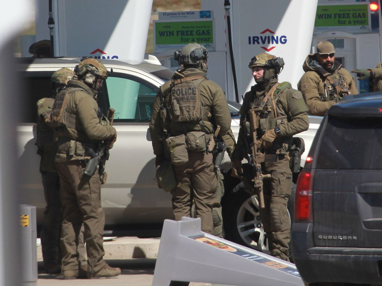 Four officers, in olive fatigues, body armor, and helmets, stand with their hands on their rifles.