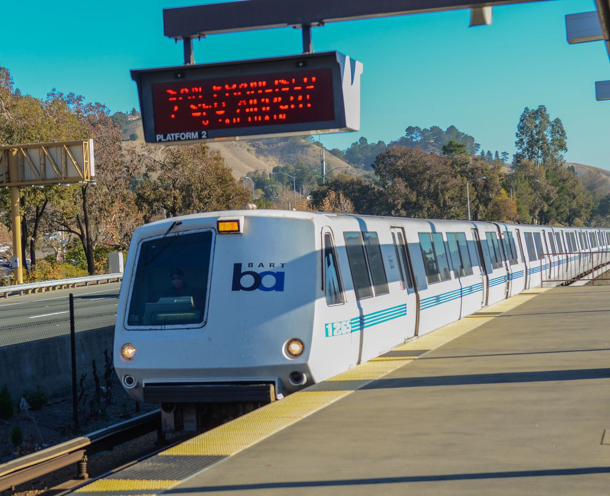 A BART train pulling into an elevated platform.