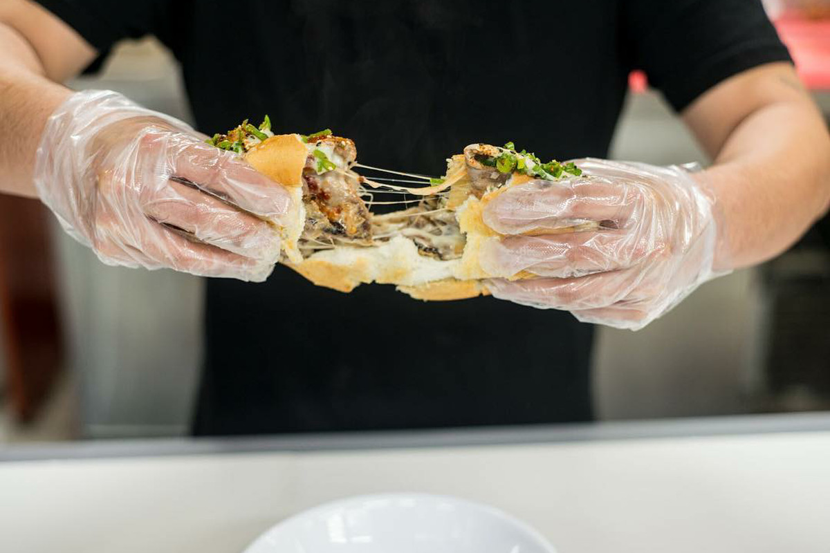 A gloved server pulls apart a Phorale sandwich, stuffed with cheese and meat