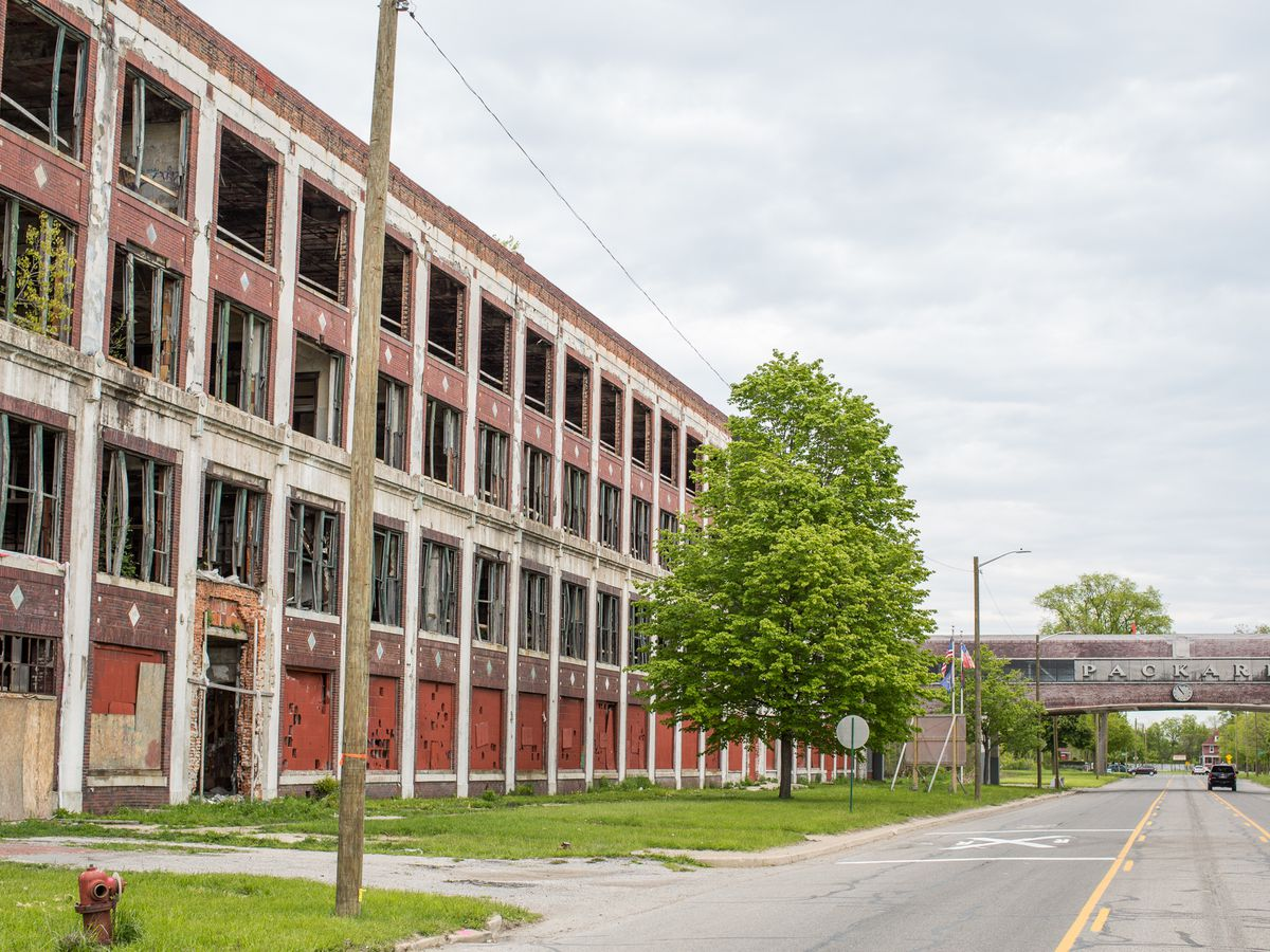 The exterior of an automotive plant in Detroit. The building has many windows and trees to the side of it.