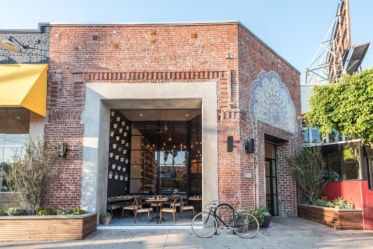 A sunny exterior for a restaurant in Silver Lake, with brick, a small front patio, and yellow awning.