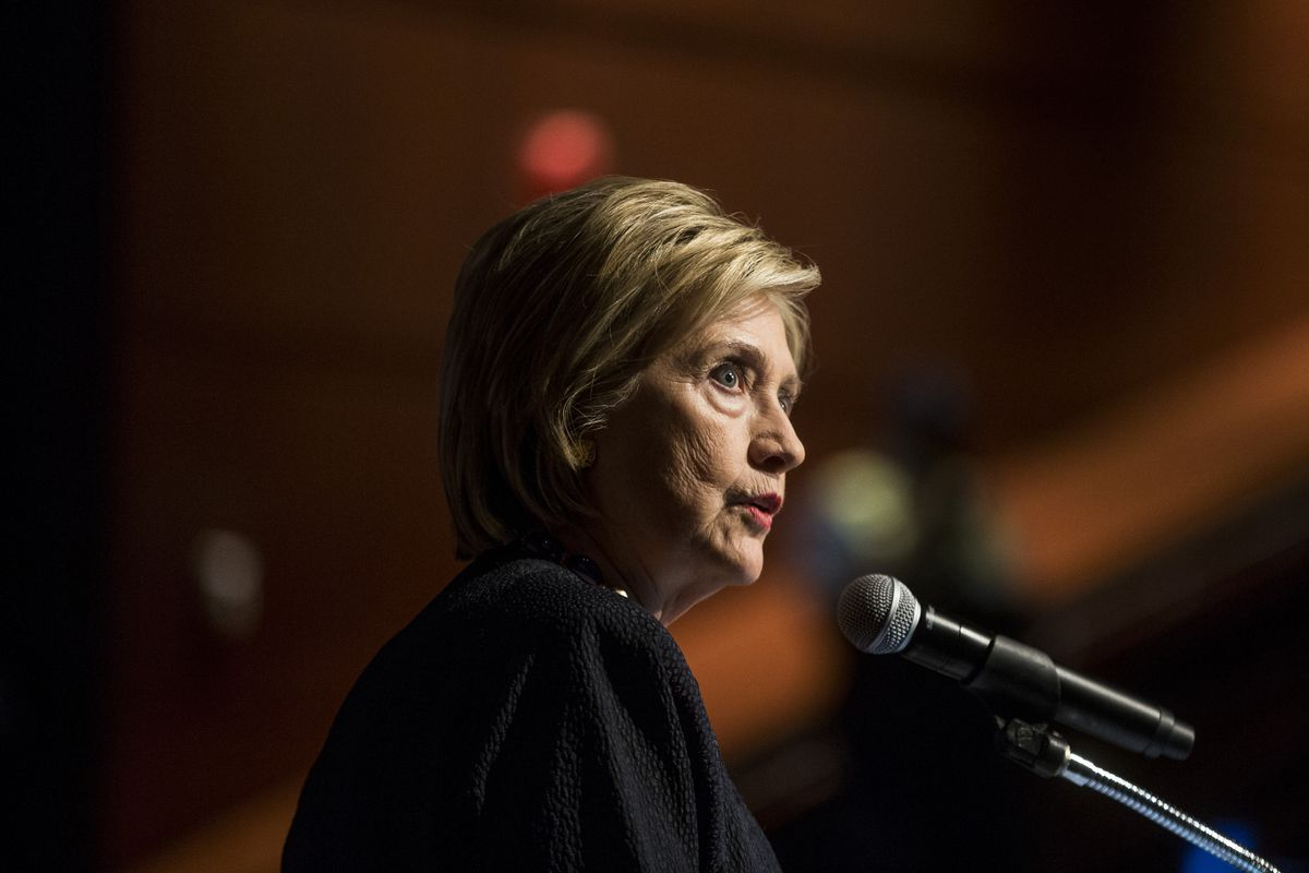 Former Secretary of State Hillary Clinton speaking into a microphone onstage.