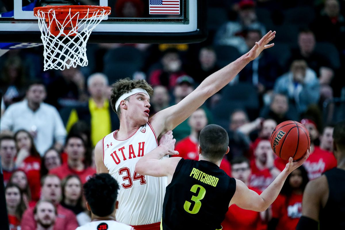 Utah Utes center Jayce Johnson defends the hoop against Oregon Ducks guard Payton Pritchard during a Pac-12 Tournament quarterfinal game at the T-Mobile Arena in Las Vegas on Thursday, March 14, 2019.