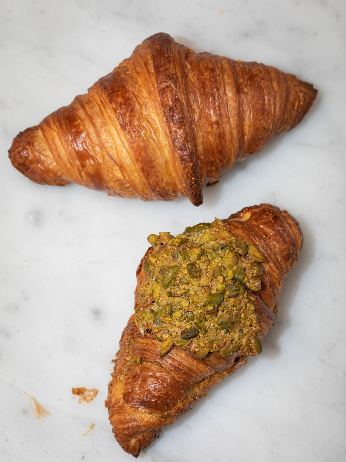 Two croissants side by side with some green chopped pistachios on top of one