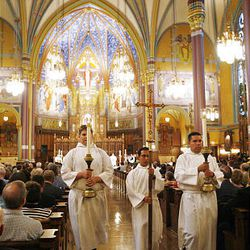 Cross and candle bearers walk through the Cathedral of the Madeleine during a service to commemorate the 100th anniversary of the cathedral, the centerpiece of Utah's Catholic culture in the community.
