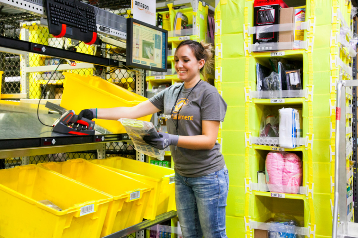 An Amazon worker loads products into bins in a fulfillment center