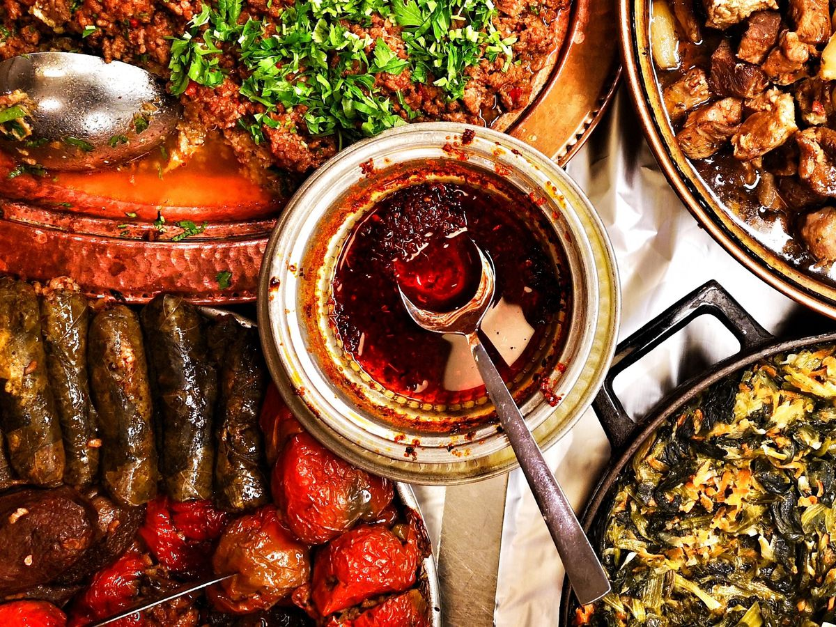 From above, a table full of dishes including stuffed grape leaves, rice, meat, and chile sauce