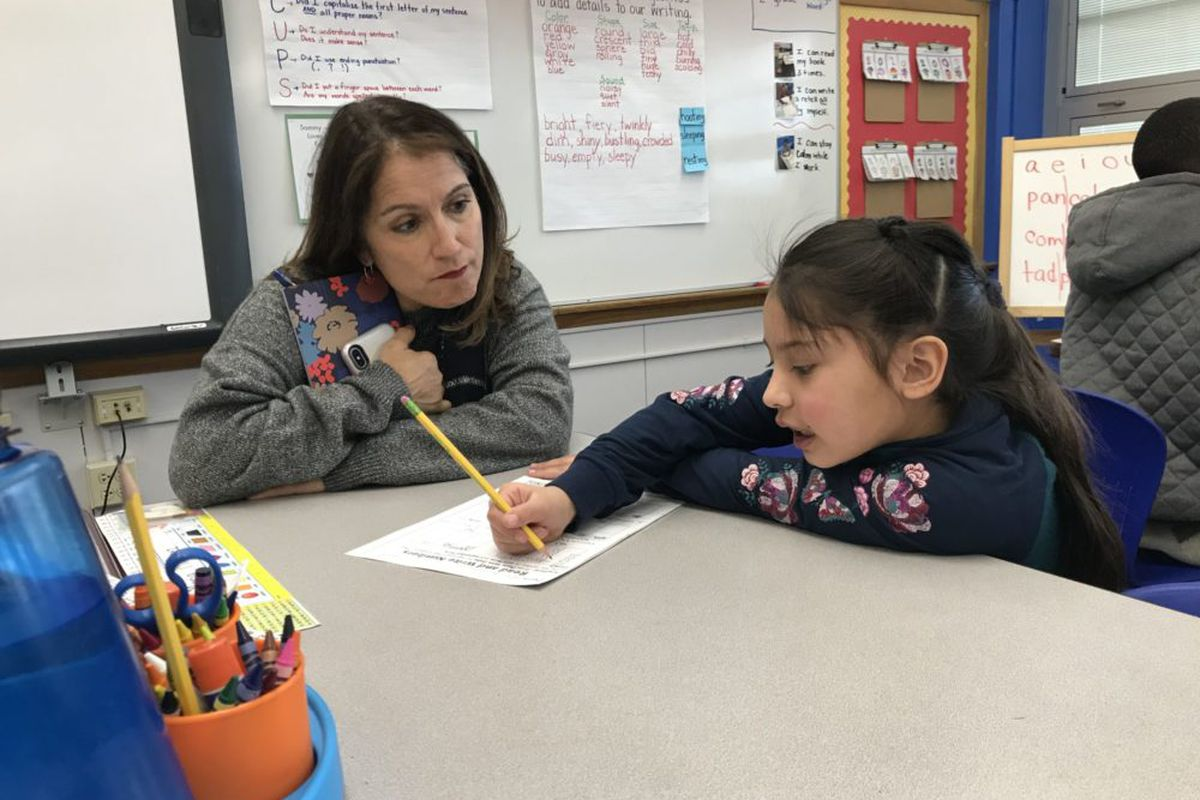 Denver Superintendent Susana Cordova leans down to watch a student work on math problems at Columbine Elementary.