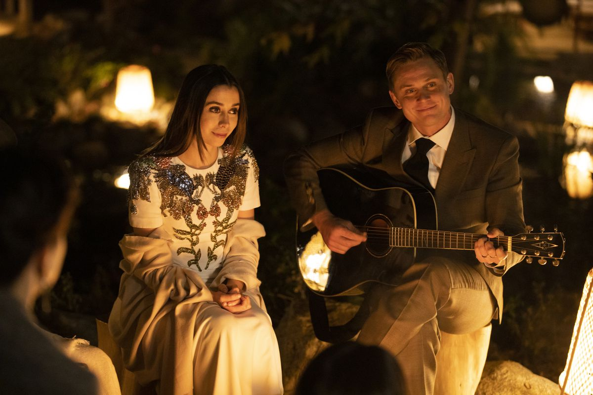 Cristin Milioti and Billy Magnussen sit together at night in a dress and suit, respectively, while Magnussen plays guitar in character as Byron Gogol.