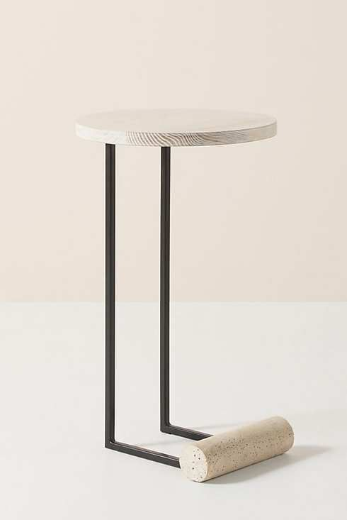 L-shaped side table with white surface and black legs.