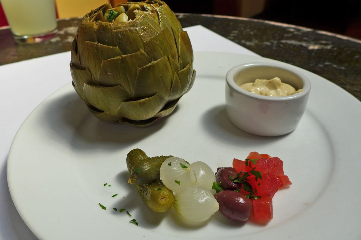 A whole artichoke with tub and mayo and cocktail onions, cornichons, chopped tomatoes and olives in a little heap on the side.