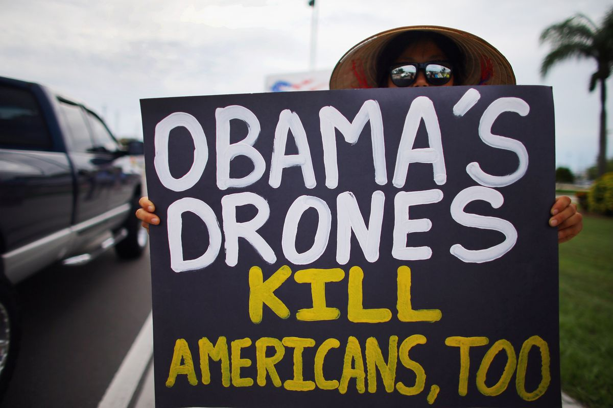Liz, who only wanted to be identified by her first name, holds a sign reading, 'Obama's Drones Kill Americans, Too,' as she joins others in a protest in front of a Raytheon company building which they say is building military drones on August 23, 2012 in