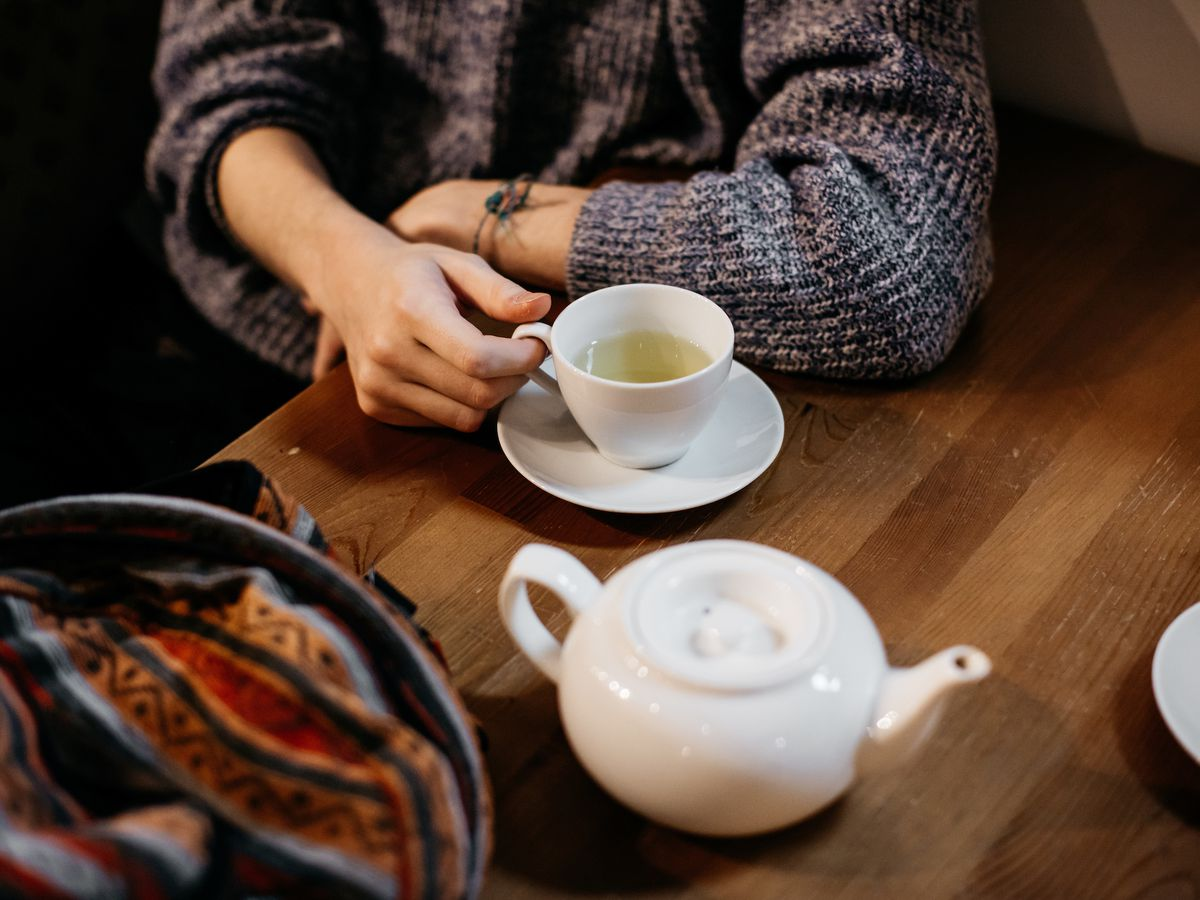A woman in a sweater grasps a white teacup filled with pale, yellow tea next to a white teapot.