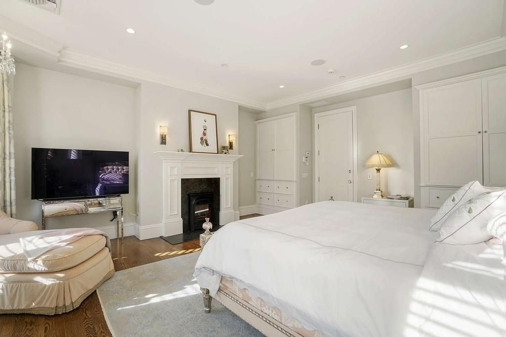 A bedroom with a large bed and an ottoman arranged around a fireplace.