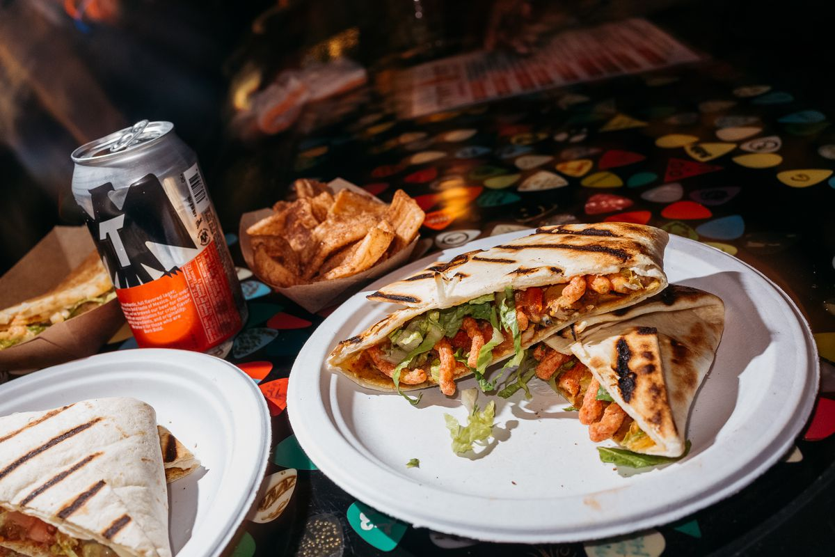 Vegan crunch wraps from a Street Beet Taco Hell pop-up. sit on a counter next to an open Tecate at PJ's Lager House.
