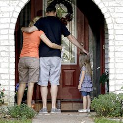 A family who identified themselves as friends of the victims, pause on the porch Thursday, July 10, 2014, after placing flowers and a framed photograph at the door of the home where a gunman killed six people Wednesday in Spring, Texas. The Harris County Sheriff?s Office says Ronald Lee Haskell was booked Thursday on a capital murder/multiple murders charge and held without bond. Authorities believe Haskell fatally shot two adults and four children on Wednesday night and critically wounded a 15-year-old girl, who called 911. (AP Photo/David J. Phillip)
