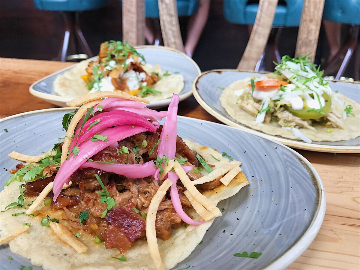 Close up of a taco topped with pickled onions; two plates with tacos in the background