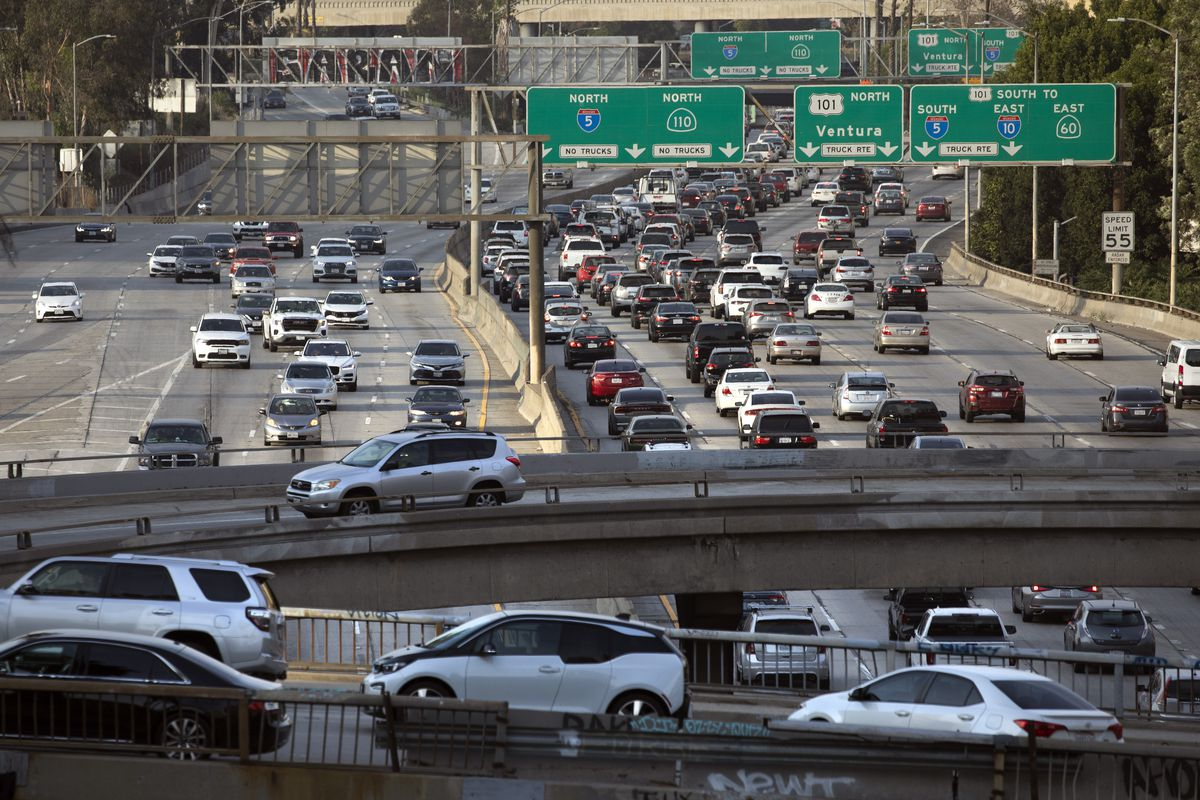 Afternoon traffic in Los Angeles with lots of cars on a wide highway crossed by overpasses.