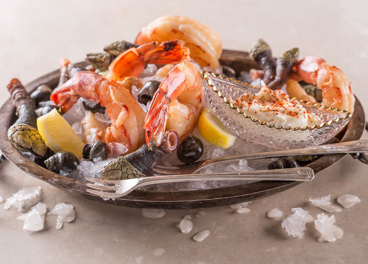 A crystal container filled with ice and topped with shrimp, cockles, and lemon slices