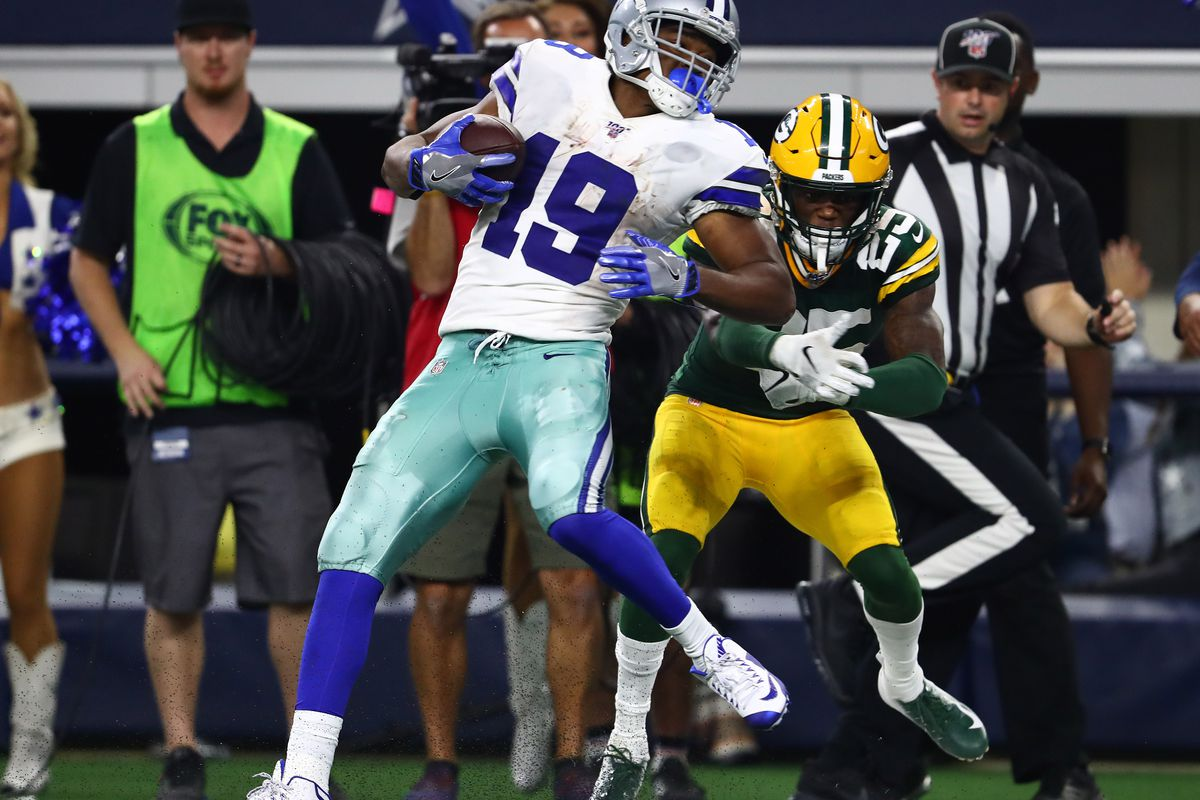 Dallas Cowboys receiver Amari Cooper runs with the ball after a reception against Green Bay Packers safety cornerback Will Redmond  for a touchdown at AT&T Stadium.