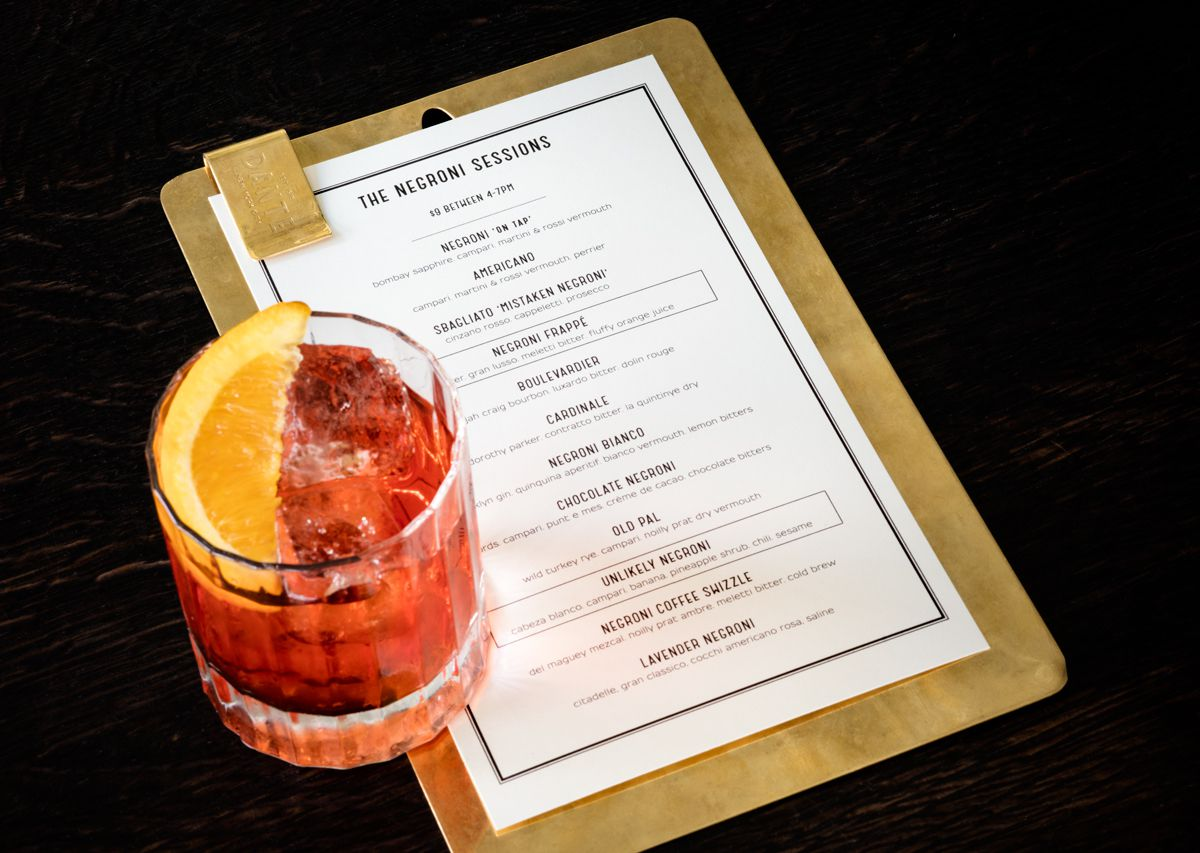 A red cocktail over ice sits on top of a menu, listening roughly a dozen types of drinks available, mostly Negronis. A slice of orange sits atop the glass.