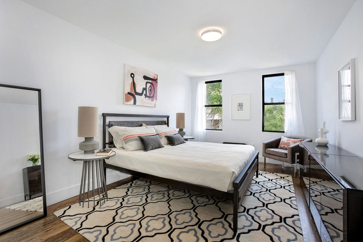A bedroom with a medium-sized bed, hardwood floors, white walls, two windows, a standing mirror, and a wooden drawer.