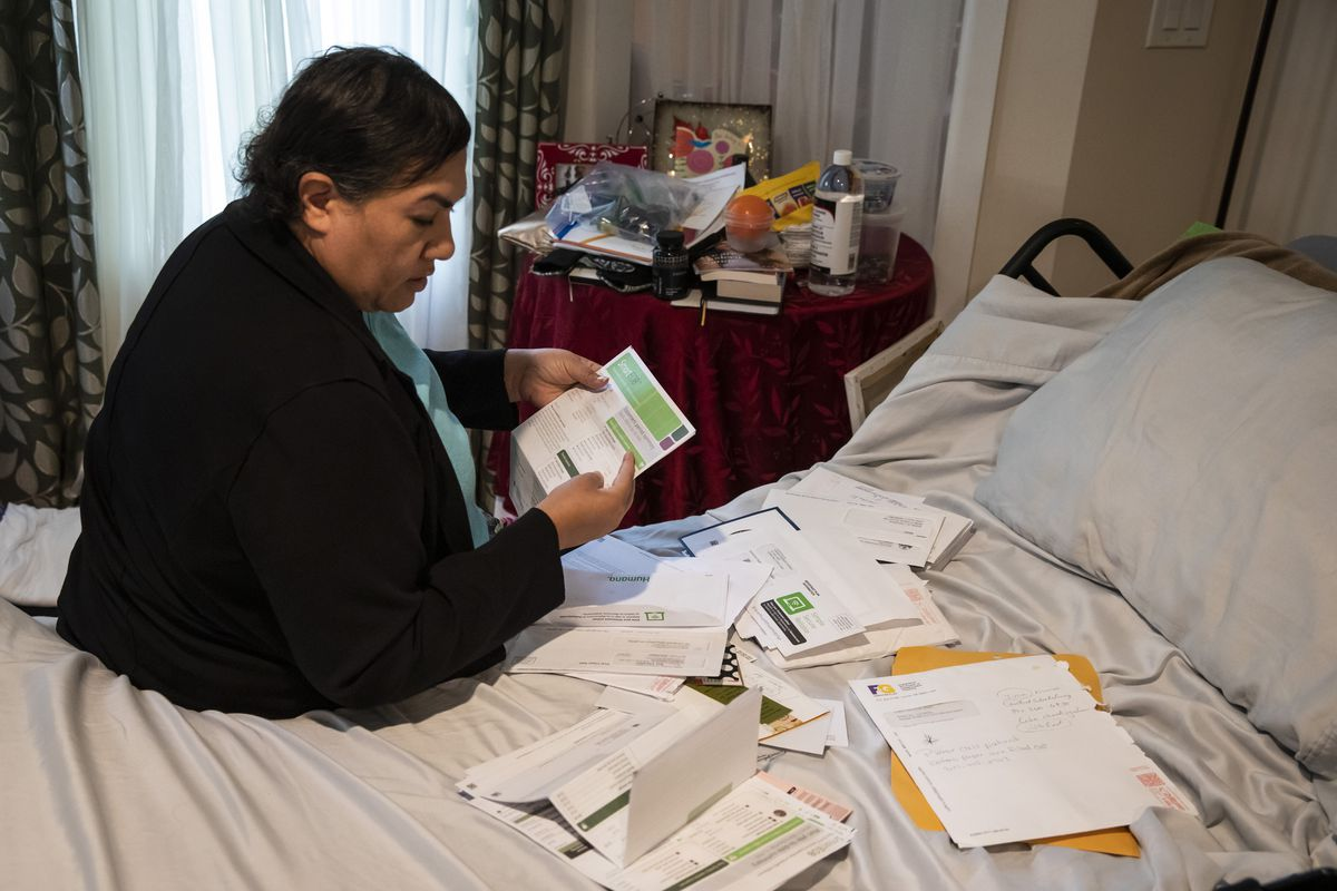 Karla Taylor-Bauman, 50, looks over her piles of medical bills as she sits on her adjustable hospital-type bed in the living room of her parents' North Chicago home, Wednesday afternoon, Sept. 16, 2020. After spending three weeks in a coma earlier this year as a result of severe complications from the coronavirus, Taylor-Bauman moved in with her parents because she requires constant care during recovery. File photo. | Ashlee Rezin Garcia/Sun-Times