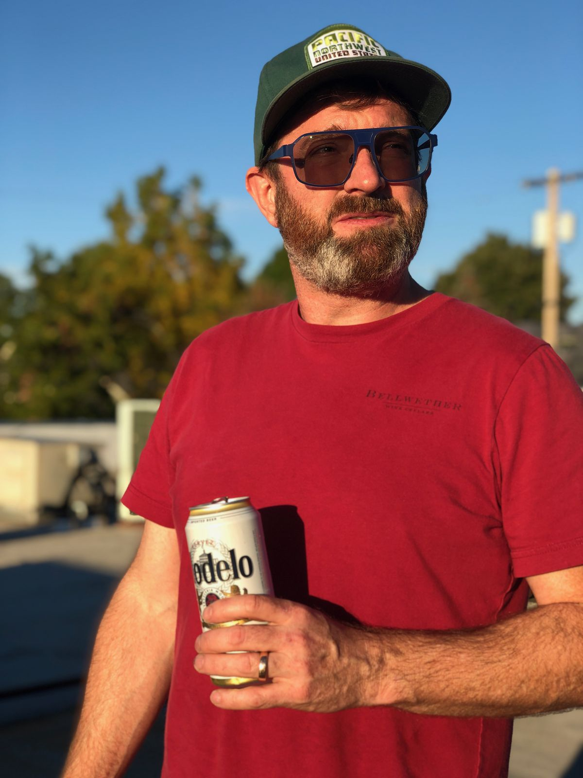 Bow & Arrow's Scott Frank, holding a can of Modelo, stands outside wearing a cap, a red t-shirt, and sunglasses.