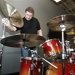 In this photo taken Thursday, Aug. 6, 2009, Steve Lavington, the director of international business for the ACM in Great Britain, arranges a drum set at the Oklahoma City campus  in Oklahoma City.