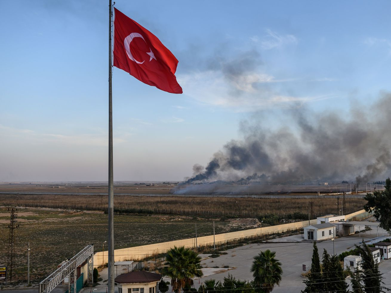 A Turkish flag flies in the foreground while smoke rises from over the border in Syria.