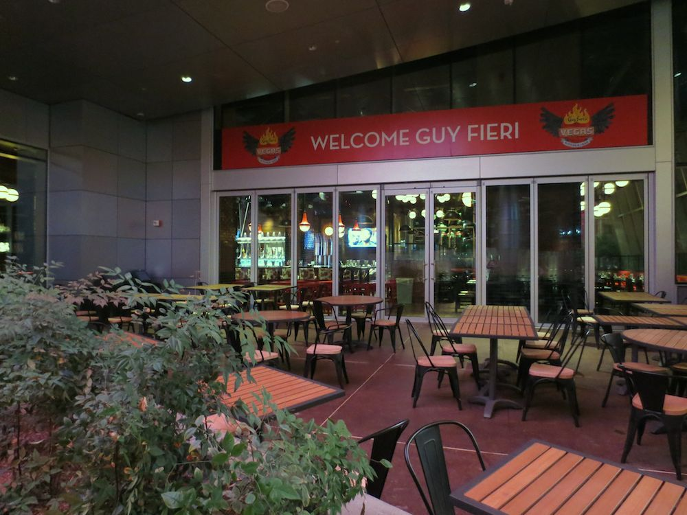 Guy Fieri's Vegas Kitchen & Bar patio with wooden tables and chairs.