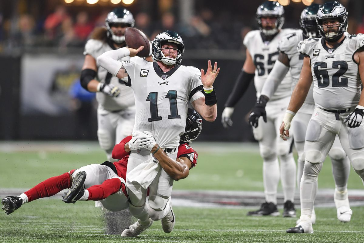 Philadelphia Eagles quarterback Carson Wentz passes while being tackled by Atlanta Falcons linebacker Vic Beasley during the fourth quarter at Mercedes-Benz Stadium.