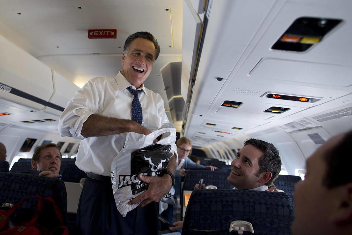 Republican presidential candidate, former Massachusetts Gov. Mitt Romney laughs as he hands out beef jerky to the press on his campaign plane, Friday, Sept. 28, 2012, in Philadelphia.