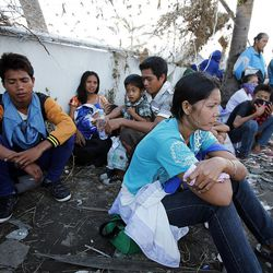 People wait at the airport in Tacloban, hoping to get transportation on a military airplane, Tuesday, Nov. 19, 2013.