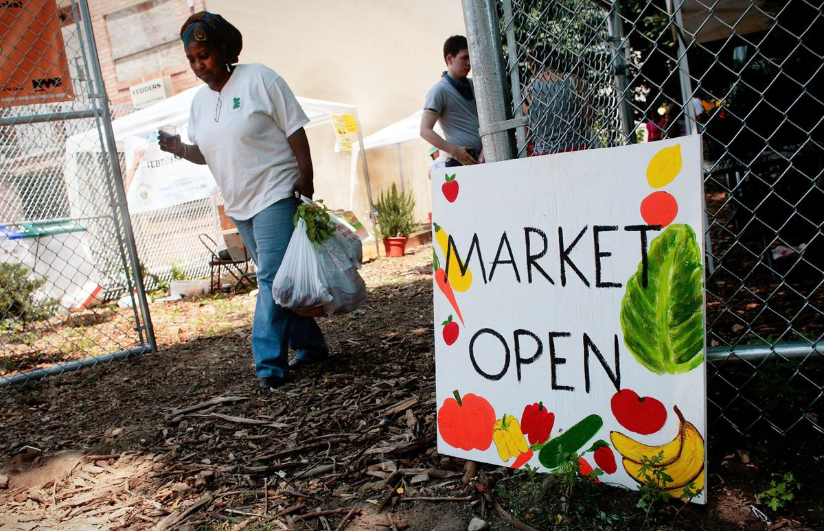 """A woman exits a farmers market with grocery bags stuffed with fresh produce. A homemade sign painted with fruits and vegetables advertises """"Market Open."""""""