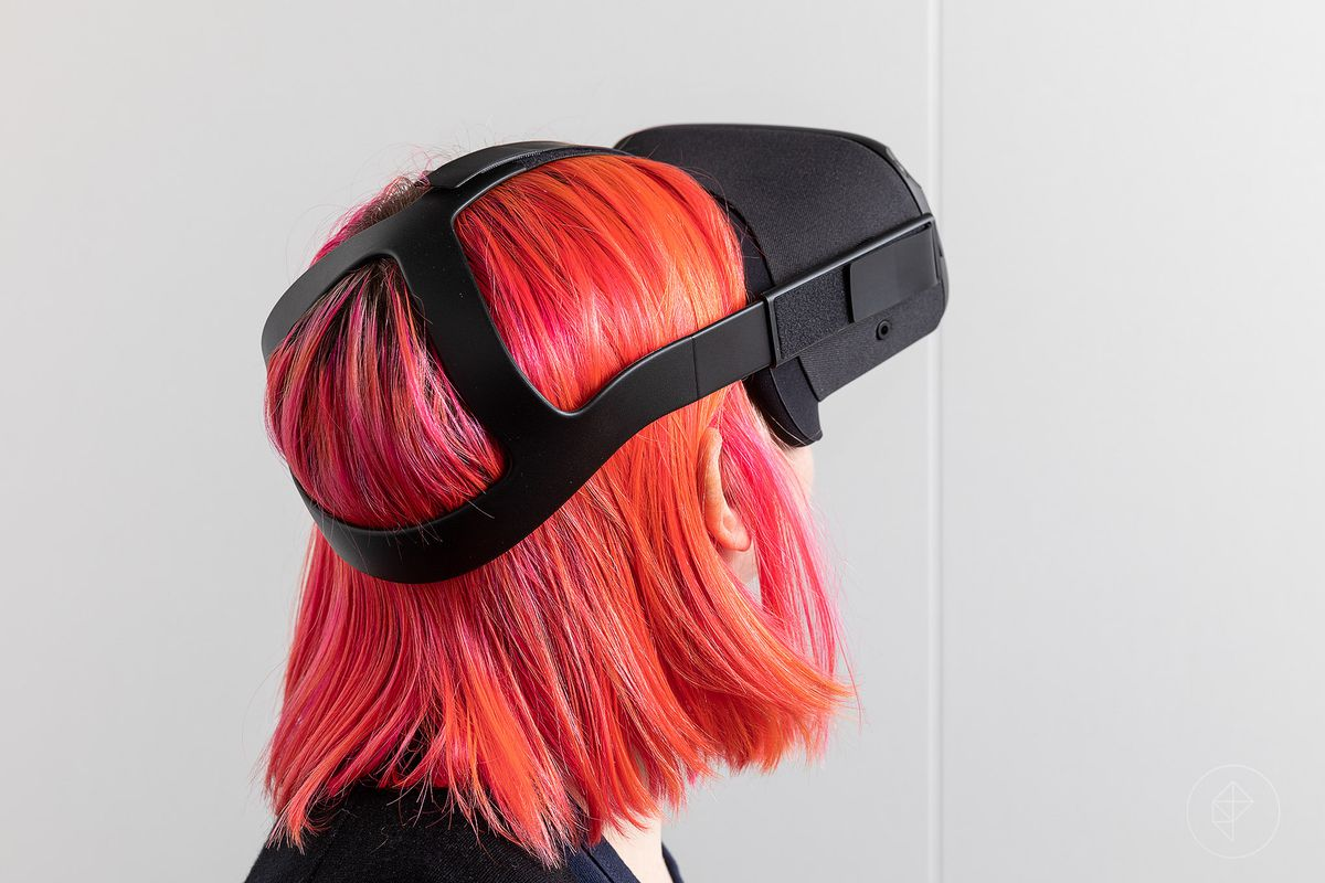Woman with bright orange and red hair wearing a VR headset
