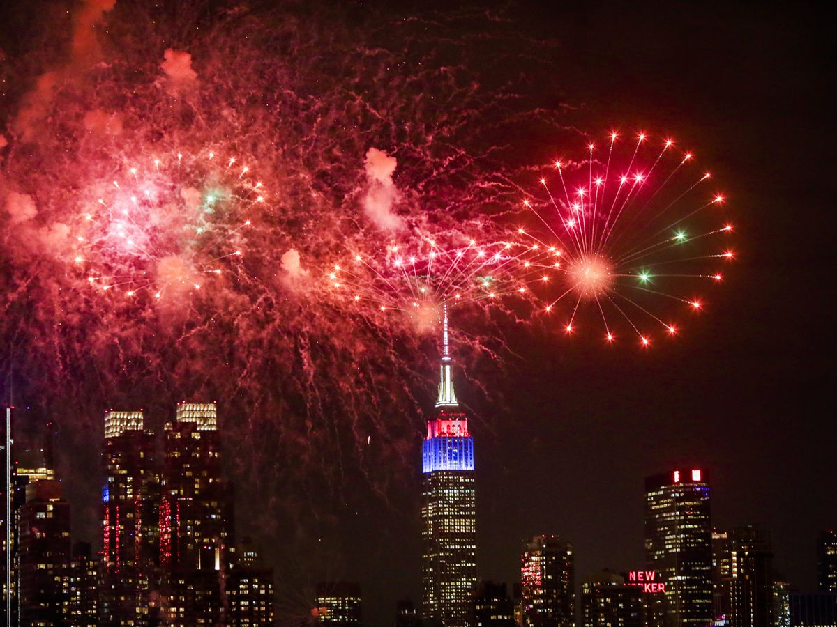 Bright red fireworks in the sky over the Empire State Building and skyscrapers in New York City.