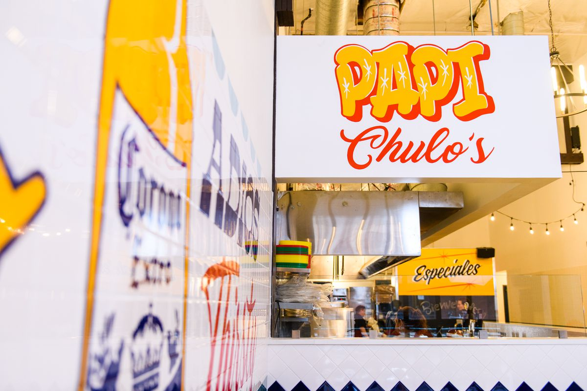"""The main kitchen area of Papi Chulo's is open format, similar to many taquerias in Mexico and California. The hood is covered by a white structure with red-and-yellow writing that reads """"Papi Chulo's"""""""