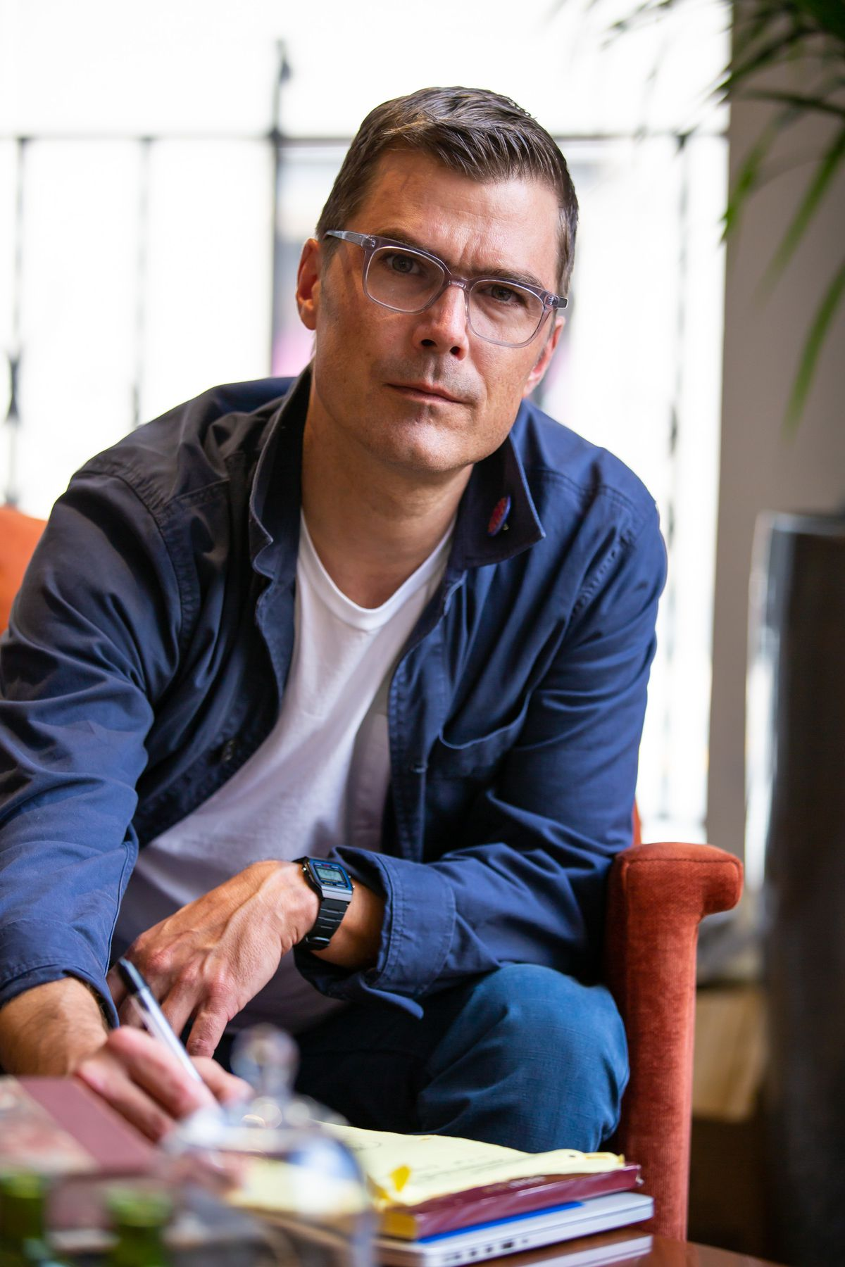 Chef Hugh Acheson wearing glasses and sitting at a table writing