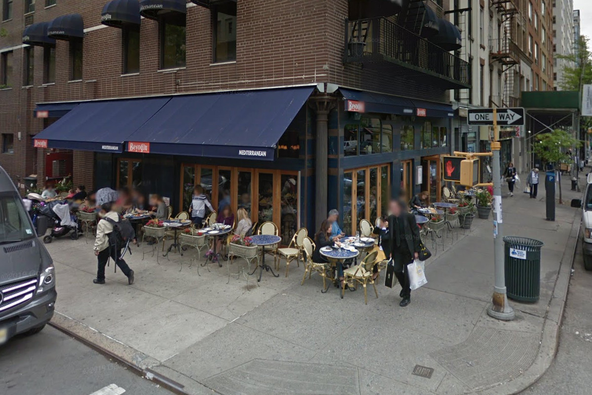 The exterior of a restaurant with a blue awning and outdoor seating