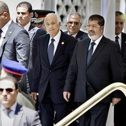 """Egyptian bodyguards surround President Mohammed Morsi, right, and Arab League Secretary-General Nabil Elaraby, second right, as they leave the Arab League headquarters in Cairo, Egypt, Wednesday, Sept. 5, 2012. Morsi says Syrian leader Bashar Assad must learn from """"recent history"""" and step down before it is too late."""