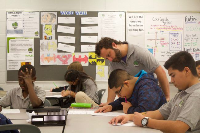 A DSST Cole Middle School teacher checks on students work during a class in November 2015.