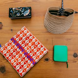 Clockwise: <b>Tsumori Chisato</b> Shell Leather Mermaid Wallet, $580; <b>Rag & Bone</b> Straw Visor, $150; Comme des Garcons Small Leather Zip Wallet, $205; <b>Claire Vivier</b> Canvas Printed Foldover Clutch, $115