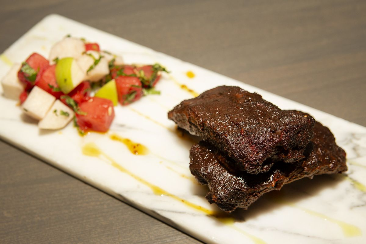 A skirt steak marinated in mole and spices on a rectangle plate with a small onion/tomato salad.