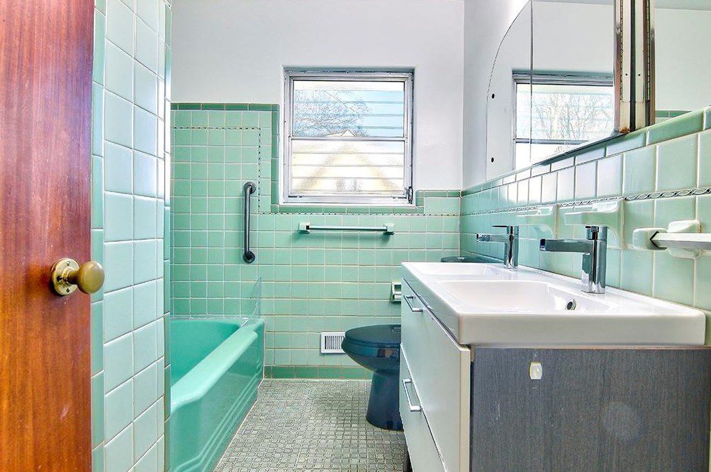 A green 1950s bathroom with a modern sink.