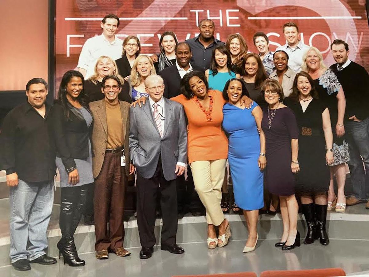 Oprah Winfrey with an arm around Bill Becker, who is beside her in the front row, in the center, in this photo of the legal team at Harpo Studios.